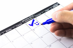 与微笑的蓝色检查。在日历的标记在2014年1月1日 免版税库存照片