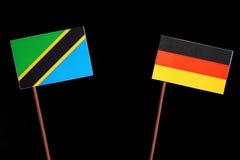 与德国旗子的坦桑尼亚的旗子在黑色 免版税库存照片