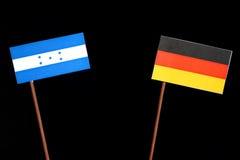 与德国旗子的洪都拉斯旗子在黑色 免版税库存图片