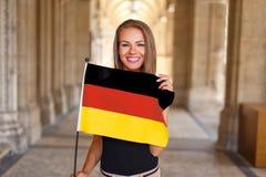 与德国的旗子的少妇微笑 免版税图库摄影