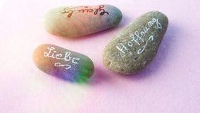 与德国词的石头爱的,在桃红色后面相信并且希望 免版税图库摄影