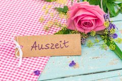 与德国词的礼品券, Auszeit,意味与玫瑰色花的暂停 库存图片