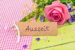与德国词, Auszeit的礼品券,意味与花花束的暂停  免版税库存照片