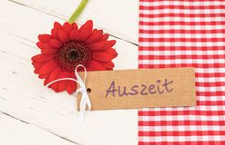 与德国词, Auszeit,手段暂停的红色花和礼品券或放松 免版税库存照片