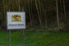 与徽章的白色高速公路边界标志拜仁,德国,翻译用英语:Freestate巴伐利亚 免版税库存图片