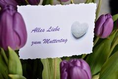 与徽章Alles Liebe zum Muttertag的紫色郁金香 免版税库存照片