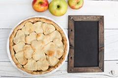 与心形的外壳顶部的苹果饼与黑板 库存照片