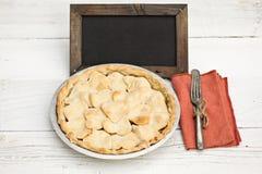 与心形的外壳顶部的苹果饼与黑板 图库摄影