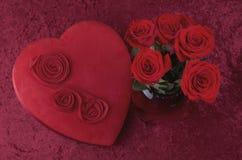 与心形的巧克力箱子和英国兰开斯特家族族徽花束的华伦泰主题的背景在红色被击碎的天鹅绒背景 免版税图库摄影