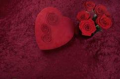与心形的巧克力箱子和英国兰开斯特家族族徽花束的华伦泰主题的背景在红色被击碎的天鹅绒背景 免版税库存图片