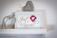 与心形的挂衣架的婚礼之日概念和在白色架子的照片框架 库存图片