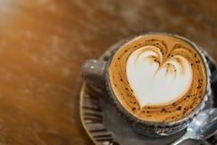 与心形的泡沫的热的咖啡在木桌上 图库摄影