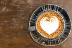 与心形的泡沫的热的咖啡在木桌上 免版税库存照片