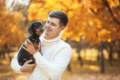 与心爱的狗的愉快的业余时间!停留在秋天晴朗的公园的英俊的年轻人微笑和拿着逗人喜爱的小狗达克斯猎犬 库存照片