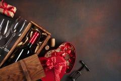 与心脏、酒、拔塞螺旋、玻璃、礼物、一个心形的箱子和黑板的情人节 库存图片