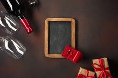 与心脏、酒、拔塞螺旋、玻璃、礼物、一个心形的箱子和黑板的Alentine的天 免版税库存照片