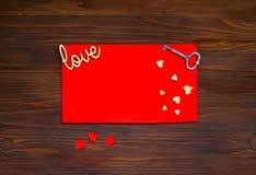 与心脏和一把钥匙的红色信封在木背景,华伦泰` s天,顶面viewn的概念 免版税库存照片