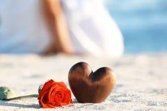 与心脏在沙子和夫妇的红色玫瑰在背景 库存照片