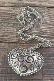 与心脏垂饰的银色项链在木背景 免版税库存图片