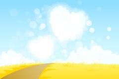 与心脏形状云彩的黄色风景 免版税库存照片