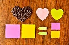 与心脏形状和五颜六色的棍子笔记的咖啡豆 免版税库存照片