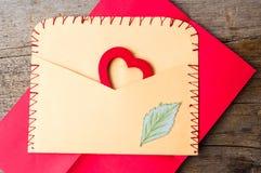 与心脏形状的信封在木背景 免版税库存图片
