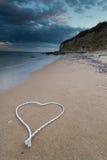 与心脏形状的白色绳索在海滩 免版税图库摄影