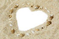 与心脏形状的贝壳在沙子 免版税库存照片