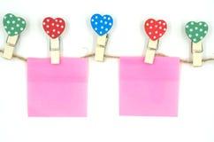 与心脏形状设计和桃红色纸板料的五颜六色的在白色背景华伦泰概念的晒衣夹和绳索隔绝的 免版税库存图片