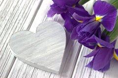 与心脏标志虹膜的静物画在白色木背景开花 婚姻 图库摄影