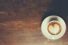 与心脏样式的咖啡在木背景的一个白色杯子 免版税图库摄影
