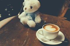 与心脏样式的咖啡在木背景的一个白色杯子 库存照片