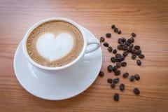与心脏样式的热的咖啡在白色杯子 免版税库存照片