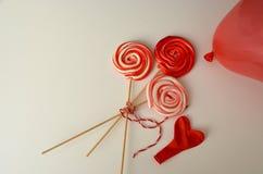 与心脏气球的红色甜糖果 愉快的华伦泰` s天有黑背景 库存图片
