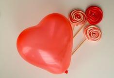 与心脏气球的红色甜糖果 愉快的华伦泰` s天有黑背景 库存照片