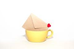 与心脏的信封在白色背景的黄色杯子 免版税图库摄影