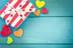 与心脏的圣诞节礼物在蓝色木桌上 免版税库存图片