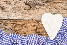 与心脏的慕尼黑啤酒节背景在蓝色检查了织品和老土气木头 免版税图库摄影