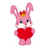 与心脏的桃红色兔宝宝在她的手上 免版税图库摄影