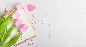 与心脏的桃红色在白色木桌的郁金香和小珠 库存照片