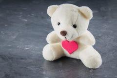 与心脏的白色玩具玩具熊在灰色背景 标志 库存照片