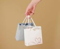 与心脏的空白两纸礼物袋子嘲笑在手中举行 em 免版税库存照片