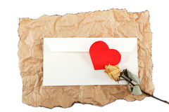 与心脏的空白的信封和在被弄皱的纸的一朵玫瑰。 库存图片