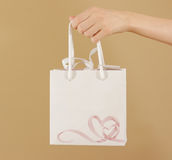 与心脏的空白的白皮书礼物袋子嘲笑在手中举行 免版税图库摄影