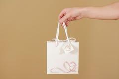 与心脏的空白的白皮书礼物袋子嘲笑在手中举行 图库摄影