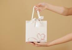 与心脏的空白的白皮书礼物袋子嘲笑在手中举行 免版税库存图片