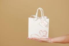与心脏的空白的白皮书礼物袋子嘲笑在手中举行 免版税库存照片