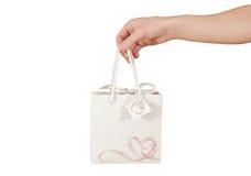 与心脏的空白的白皮书礼物袋子嘲笑在手中举行 库存图片