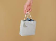 与心脏的空白的蓝纸礼物袋子嘲笑在手中举行 e 免版税图库摄影
