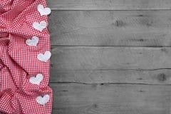 与心脏的红色和白色方格的框架在木背景 图库摄影